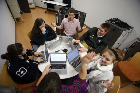 Students sit around a table with computers discussing technology