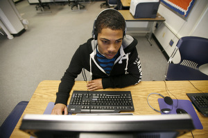 Student working on a computer using headphones